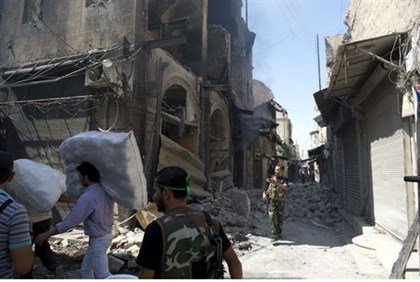 Syrian civilians walk past the rubble of buildings in Aleppo