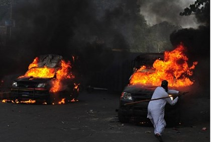 A Pakistani Muslim demonstrator hits a burning police vehicle during a protest