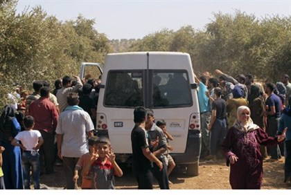 Syrian refugees receive food rations near Turkish border