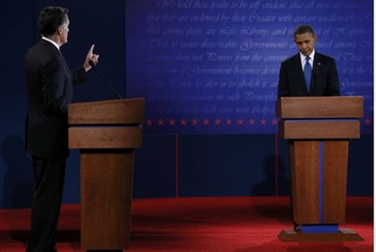President Barack Obama listens as Republican presidential nominee Romney speaks during the first pre