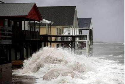 A wave crashes over the protecting sandbags in front of the houses on the east side of Ocean Isle Be