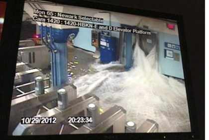 Flood waters rush into a PATH train station in Hoboken, NJ