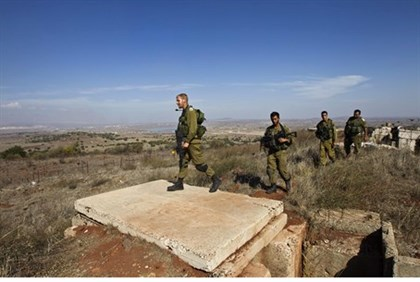 Israeli soldiers patrol the area near the Syrian border