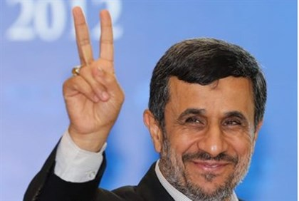 Ahmadinejad gives a sign to photographers in Indonesia