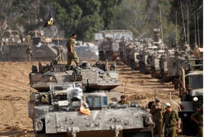 Israeli soldiers prepare armored personnel carriers (APC) at an area near Gaza