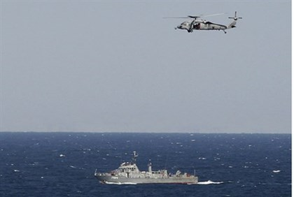 helicopter from US aircraft carrier over Iranian ship in Strait of Hormuz