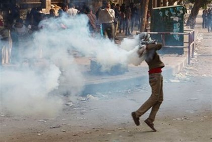 A protester runs to throw a tear gas canister back at police during clashes with police near Tahrir