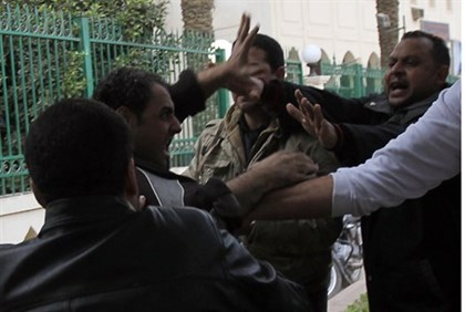 Morsi supporters fight with an anti-Morsi protester outside the presidential palace in Cairo