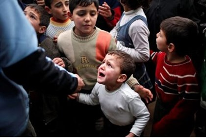A Syrian child refugee cries in a queue waiting to receive aid in Syria near the Turkish border