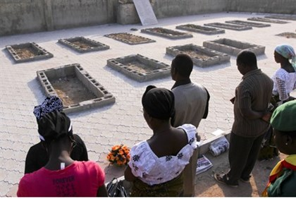 People pray near the graves of victims of an attack in Nigeria