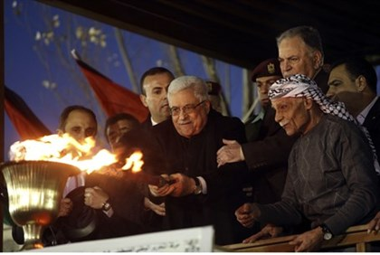 Abbas lights a torch during a rally marking the 48th anniversary of the founding of Fatah