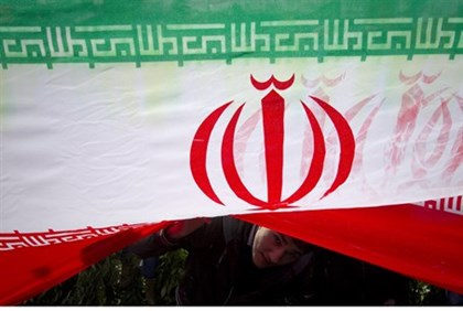 A demonstrator peeks from under an Iranian flag