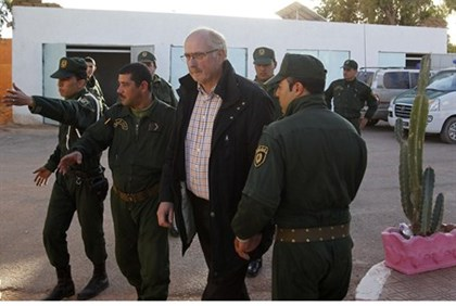 Algerian security escorts a freed hostage