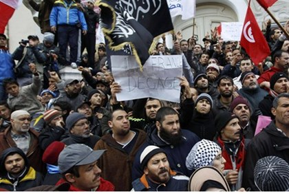 Protesters shout slogans and wave flags during a demonstration in support of the ruling party Ennahd