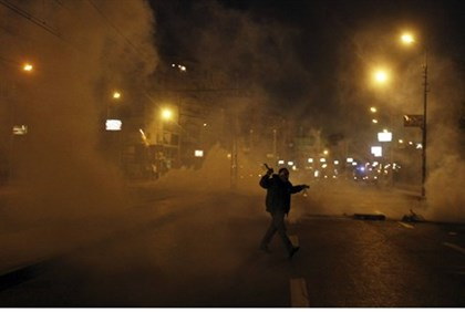 Protester flees from tear gas in front of the presidential palace