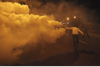Anti-Morsi protester throws a tear gas canister