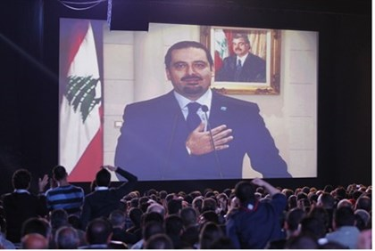 Saad al-Hariri greets his supporters via a televised screening