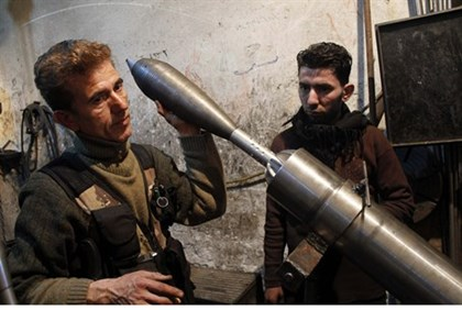 A Free Syrian Army fighter holds an improvised mortar shell