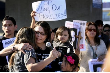 Protesters hug and show support for victims killed by Border Patrol agents