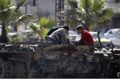 Children play on damaged tank in Aleppo