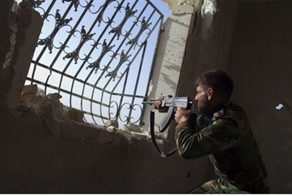 Rebel fighter aims his weapon towards Syrian government forces near Aleppo