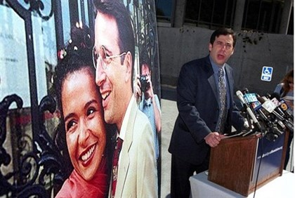 A friend of Daniel Pearl speaks to reporters next to a wedding photo of Pearl and his wife Mariane