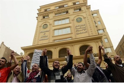 Muslim Brotherhood members gather in front the party's headquarters in Cairo