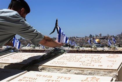 An Israeli soldier placing a flag on the grave of a friend on Yom Hazikaron