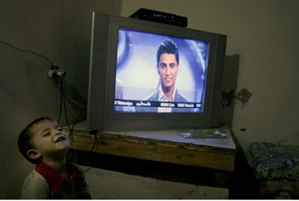 PA Arab kids watching singer Mohammad Assaf on a TV monitor