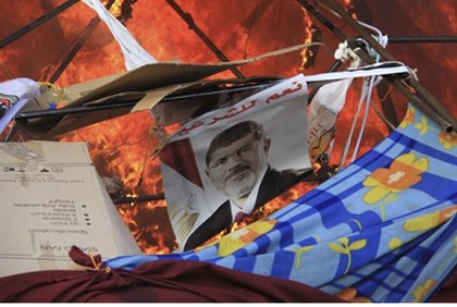 A poster of Morsi burns after police clear protesters in Cairo, 14th August 2013