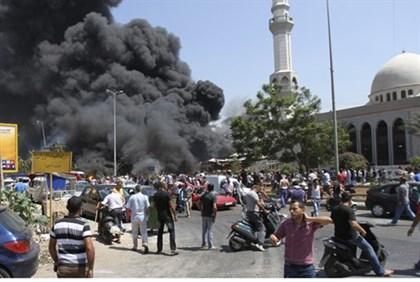Smoke rises outside al-Taqwa mosque in Tripoli after bomb attack