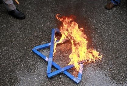 Turkish students burn a star of david at a protest outside Israeli embassy in Ankara
