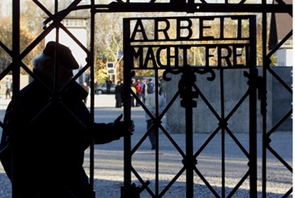 Visitor walks through a gate at the former Dachau concentration camp