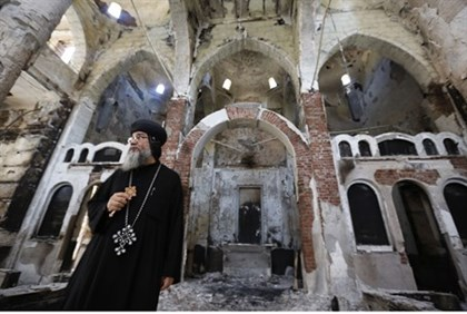 Coptic priest surveys damage to church wrought by Muslim mob