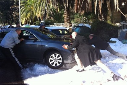 Yaalon (R) helps move stuck car
