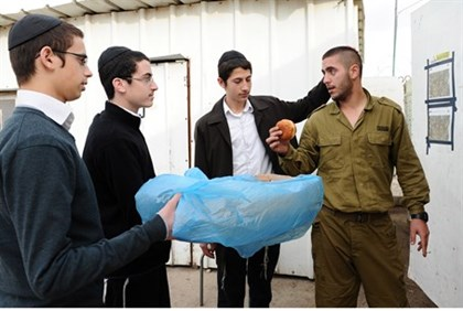 Chabad volunteers hand treats to Israeli soldiers during Hanukkah