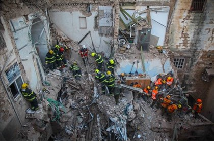 Rescue workers search for survivors at the site of Akko gas explosion