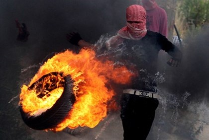 Arab rioter rolls burning tire on 'Nakba Day'