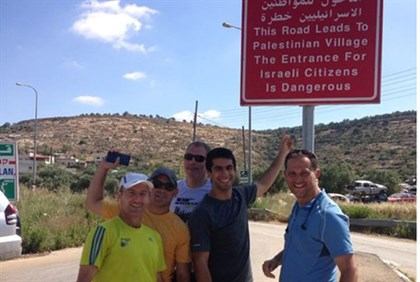Jewish group poses ironically in front of sign to Arab village
