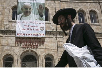 Hareidi man walks past a poster of Pope Francis in Jerusalem's Old City