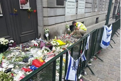 Man lays flowers at memorial outside Brussels Jewish Museum