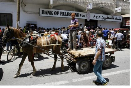Palestinian Arabs line up outside 'Bank of Palestine', Gaza City, June 2014