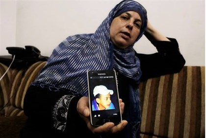 Suha Khder, mother of murdered teen Mohammed, shows a picture of him to reporters at their home