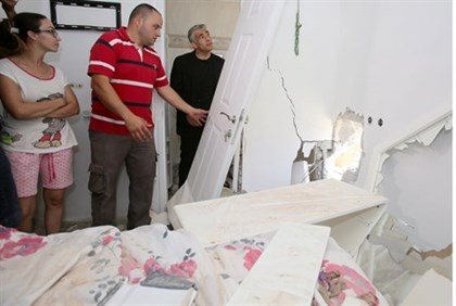 Finance Minister Yair Lapid visits a home damaged by rocket fire in Sderot