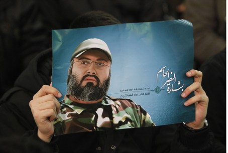Hizbullah supporter holds a poster of Mughniy