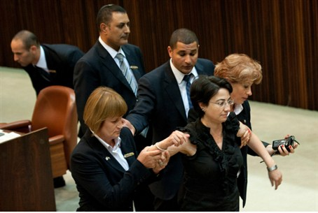 Guards escort Zoabi out of the Knesse