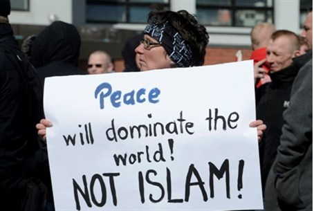 A woman holds an anti-Islamic banner during a