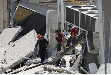 Rescue workers patrol a building which was da
