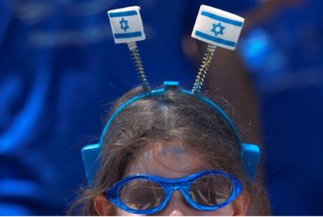 A girl wears Israeli flags on her head during