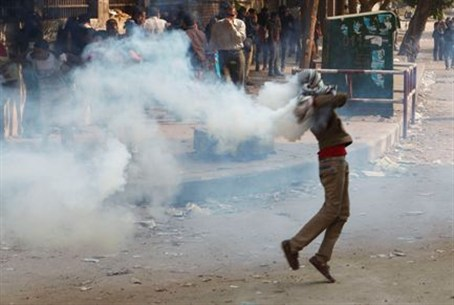 A protester runs to throw a tear gas canister